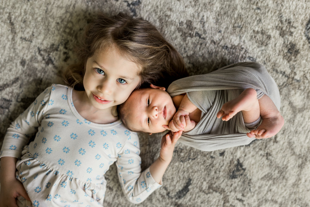 Big sister cuddling baby brother during this Houston, TX newborn lifestyle session.