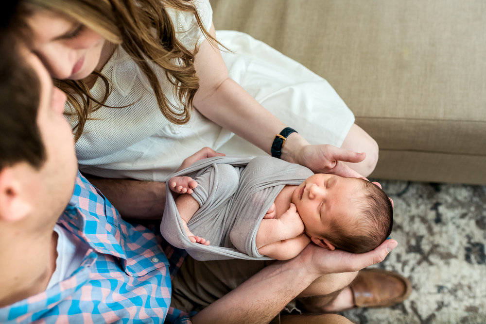Mom and Dad share a kiss over brand new baby boy during his newborn lifestyle session in Houston, TX.