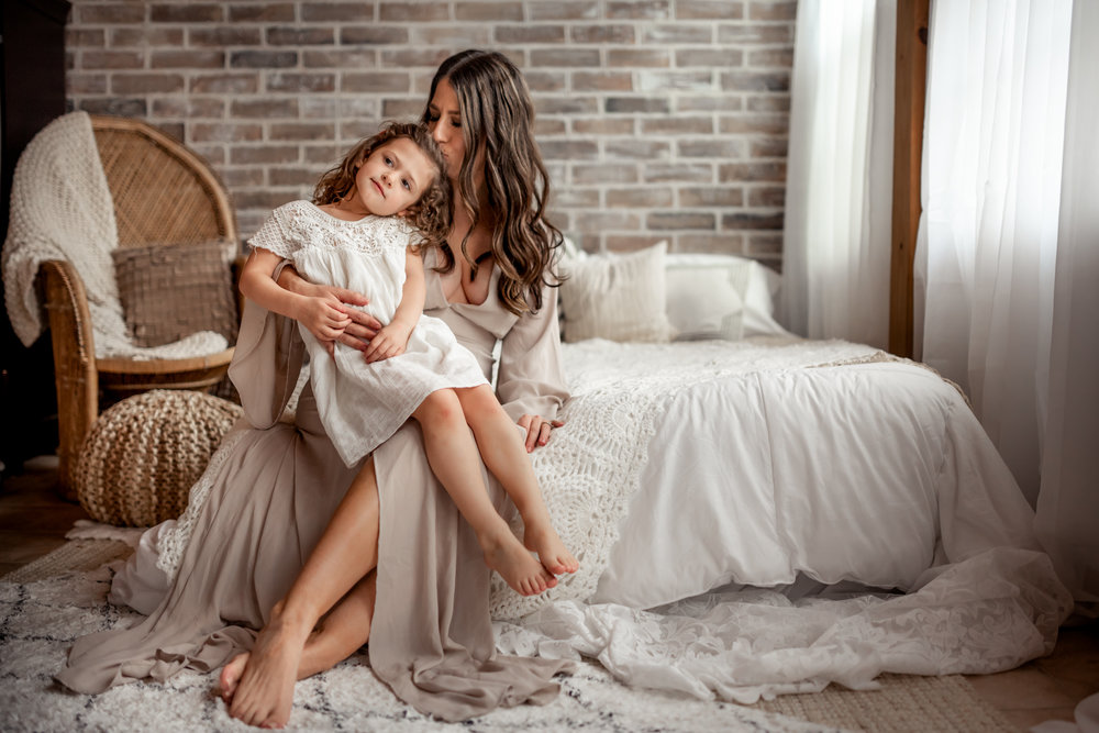 Beautiful Mommy and Me session with mom and her baby girl in a Houston, TX natural light, boho studio with a brick wall, textures accents, peacock chair, and neutral details.