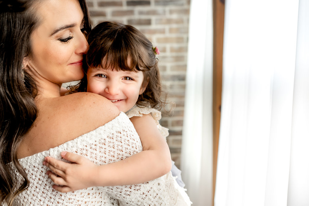 Beautiful Mommy and Me session with mom and her baby girl in a natural light, boho studio with a brick wall, textures accents, peacock chair, and neutral details. All smiles and kisses!