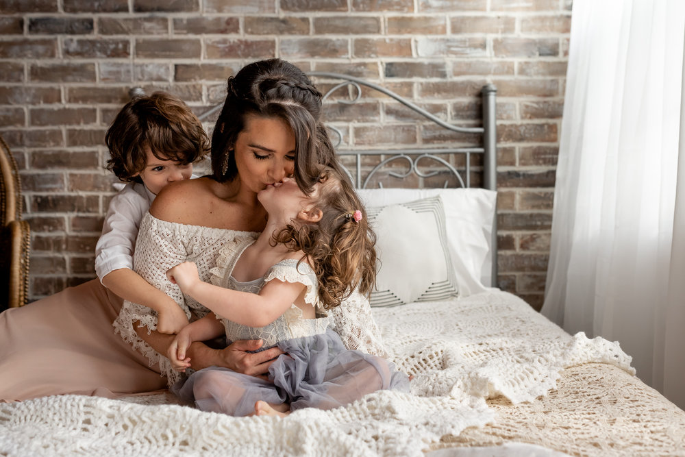 Beautiful mom and her baby girl in a natural light, boho studio with a brick wall, textures accents, peacock chair, and neutral details.