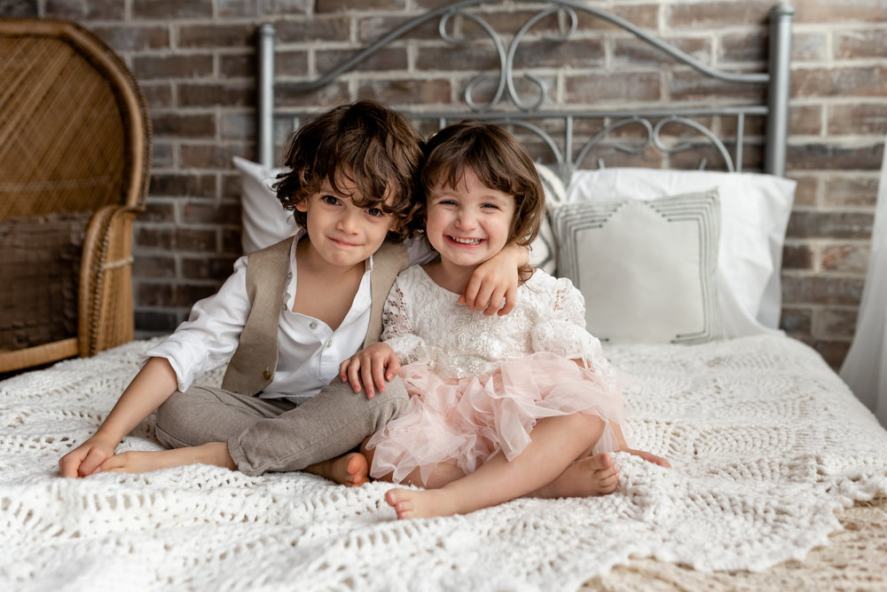 Sweet siblings in a natural light, boho studio with a brick wall, textures accents, peacock chair, and neutral details. Boy and girl, brother and sister share a sweet kiss and hug.