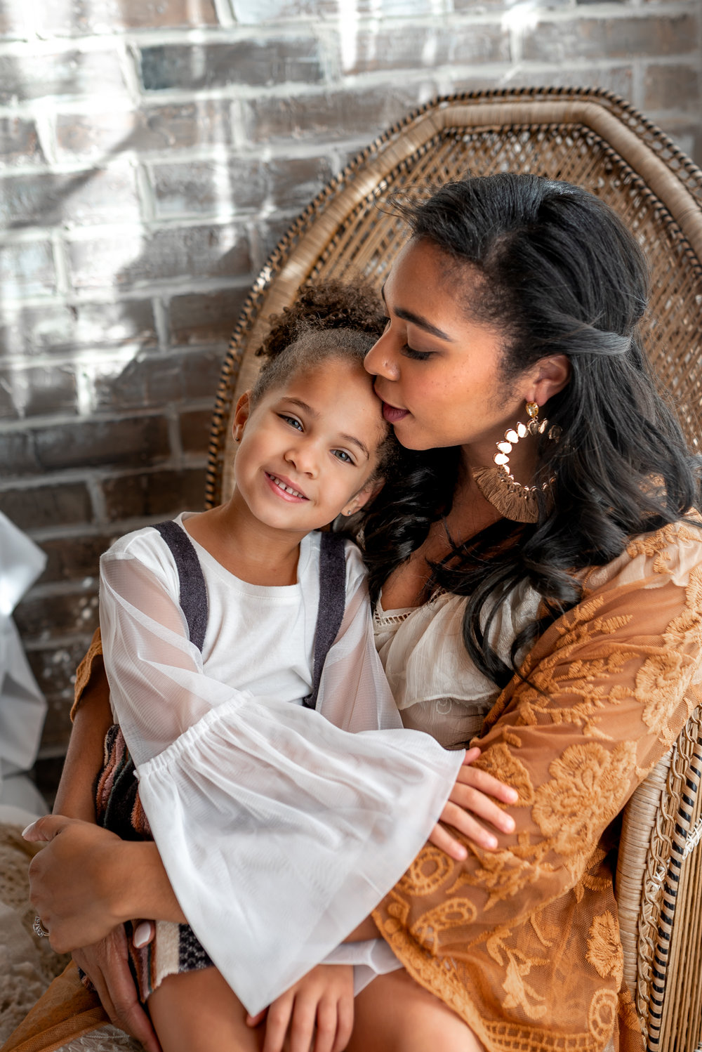 Beautiful Mommy and Me session with mom and her baby girl in a natural light, boho studio with a brick wall, textures accents, peacock chair, and neutral details.