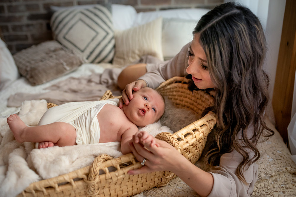 Beautiful mom and her baby boy in a Houston, TX natural light, boho studio with a brick wall, textures accents, peacock chair, and neutral details. Moses basked and soft details fill the space.