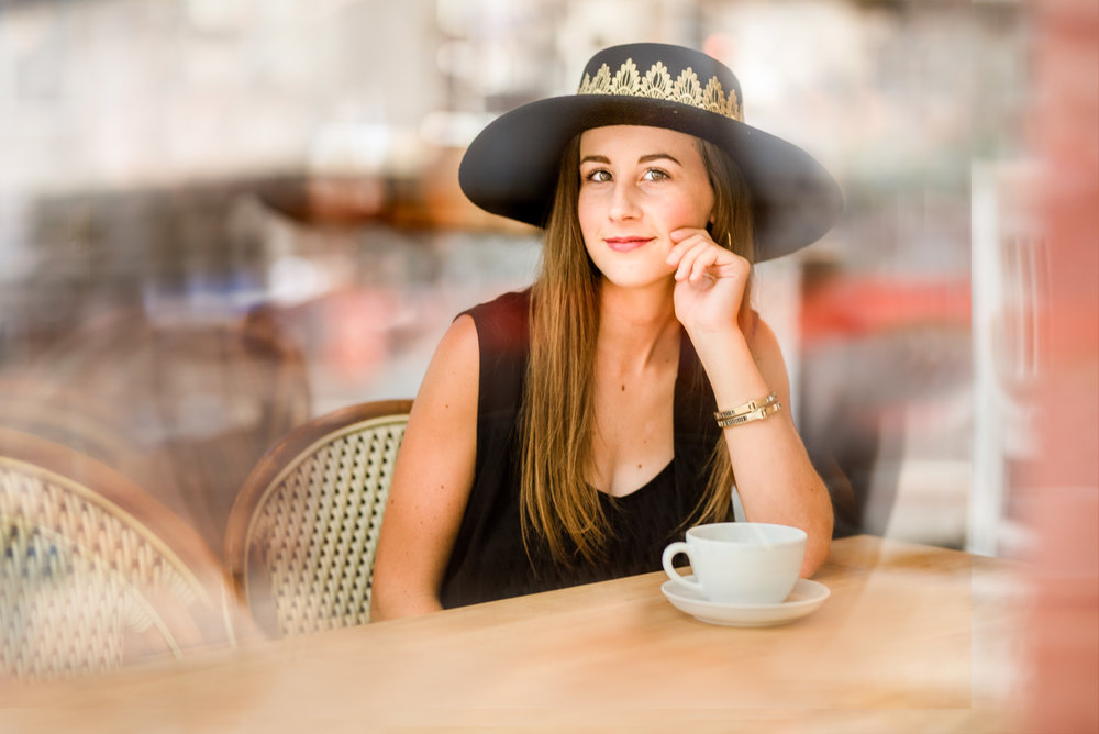 Houston, TX High School Senior girl sits in coffee shoot and smiles through window.