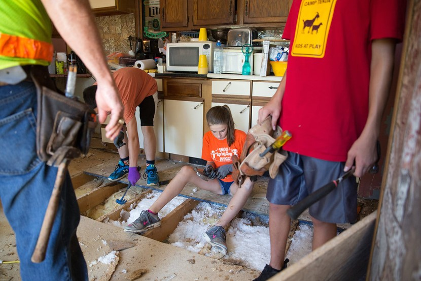 Volunteers helping to repair a kitchen floor.