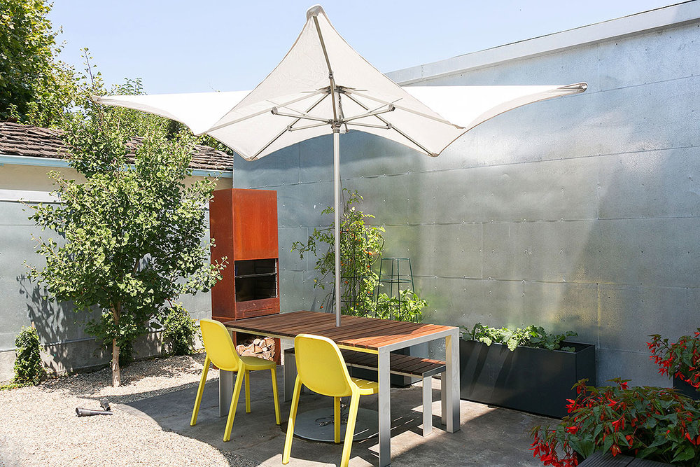 THE ZINC-CLAD STORAGE BULIDING REFLECTS LIGHT INTO THE GARDEN AND SHELTERS PLENTY OF TOOLS, BICYCLES, ETC.