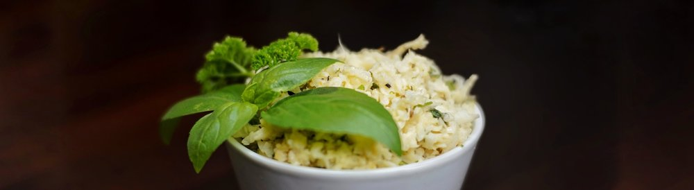 Cauli-Rice in a cup, decorated with a basil leaf.