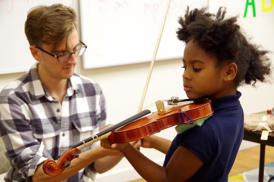 Doane and with student Laura Drone. After practicing with their box violins, students got a chance to try a few notes on a real one.