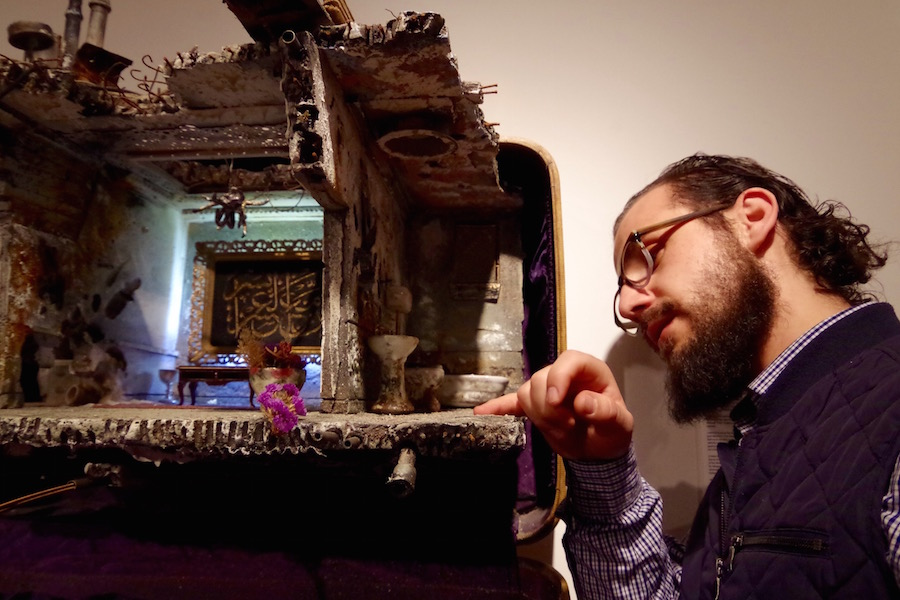 Before Monday's reception, Hafez took moments to examine each piece. Here, he pointd to where water should line the floor in Badr's miniature. Lucy Gellman Photo.