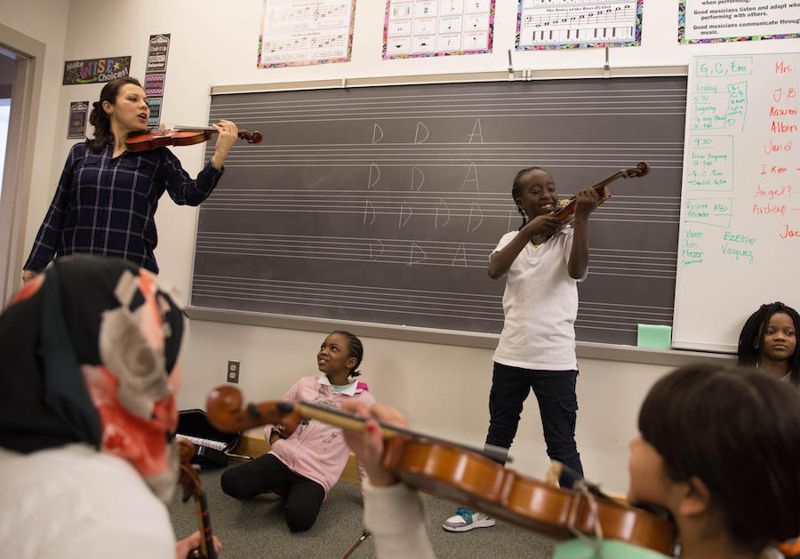 Yaira Matyakubova teaches a violin class for refugee children at Music Haven in New Haven, Conn. Photo by Ryan Caron King for WNPR.