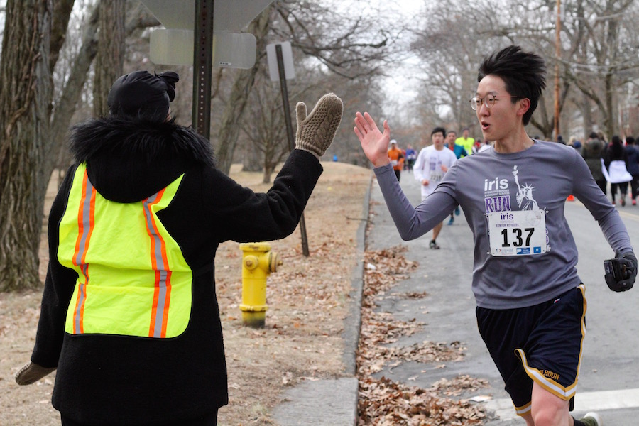 Runner Dennis Wang, a student at the Yale School of Medicine and graduate of the Yale School of Public Health, hits the three mile mark, and gets some support from a race volunteer.