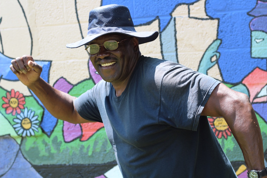 """From morning to night, I hear people on the trail"" Calvin Nelson said. The Elm City Footraces mural is on the side of his garage. ""I love it."""