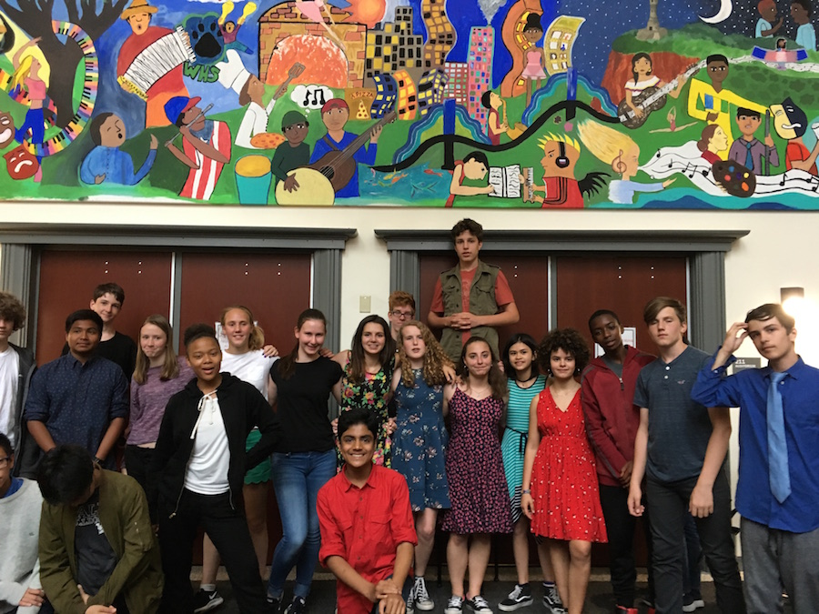 Almost all of the students in Hooker's eighth grade class gather beneath the mural.