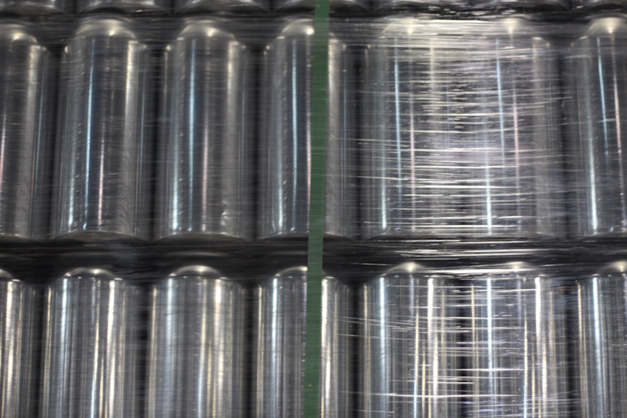 In the brew space, ceiling-high crates of cans wait to be filled.
