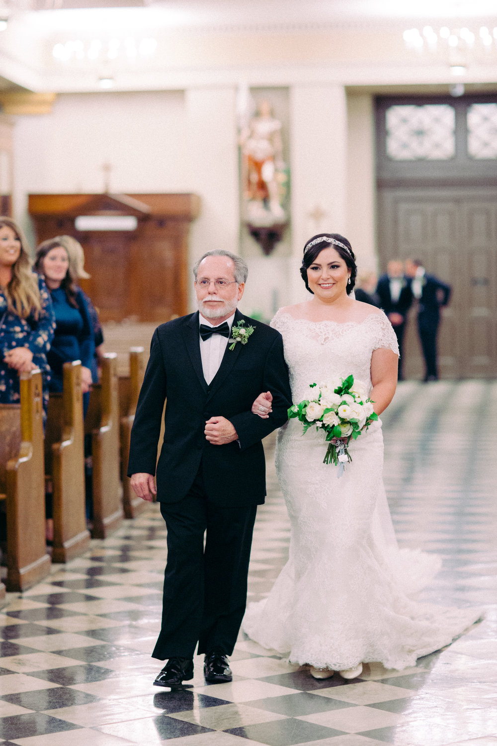bride wearing an off the shoulder lace gown by violette by ines di santo. catholic wedding in new orleans