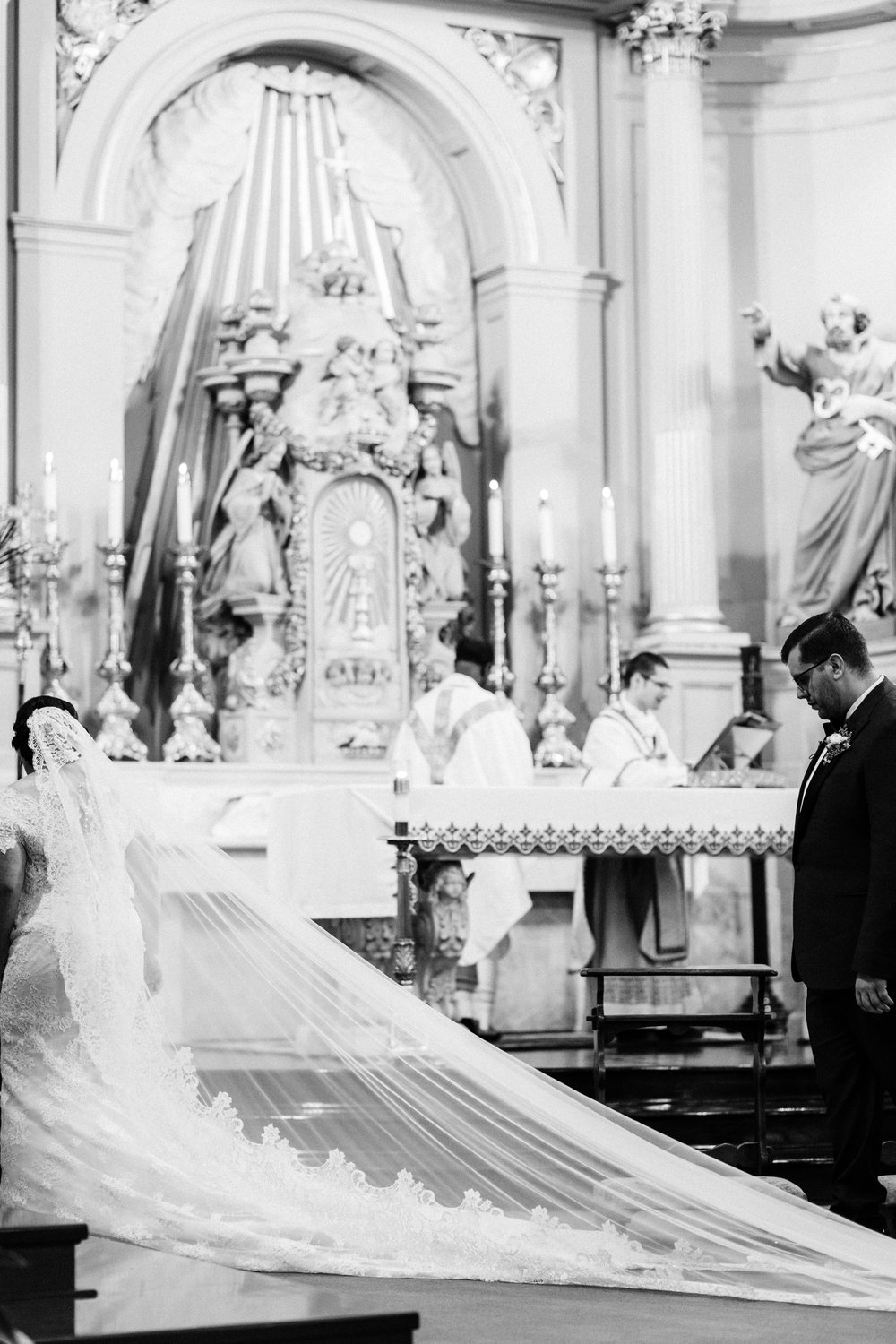 bride wearing a cathedral mantilla veil to her catholic wedding in new orleans