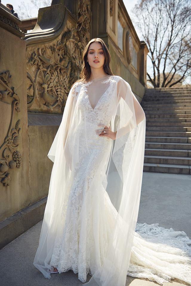 monique ;huillier lace gown with a bridal cape