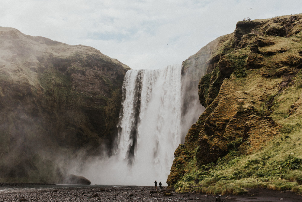 Distance shot of couple looking at Skógafoss waterfall in Iceland.jpg