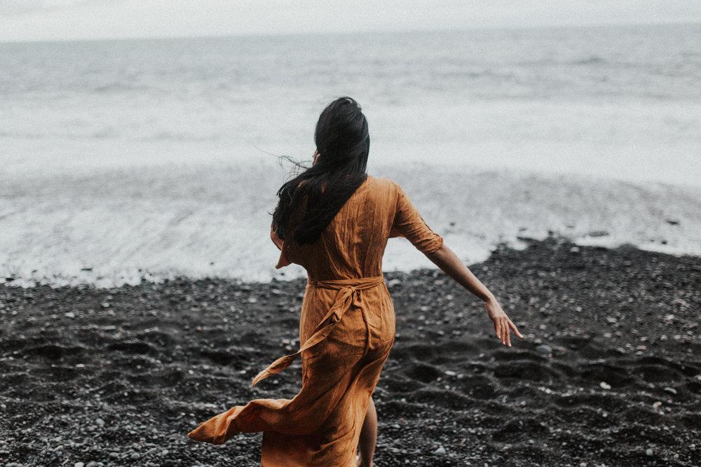 woman in flowing dress running on vik beach in iceland.jpg
