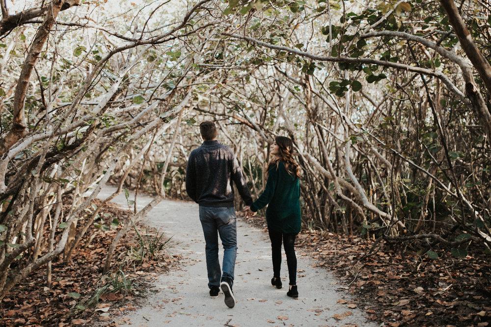 Couple walking through Florida shrubs.jpg