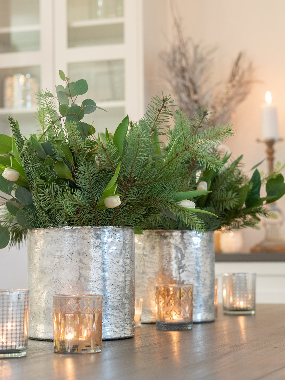 Fresh pine and eucalyptus add fragrance while white tulips break up the darkness.