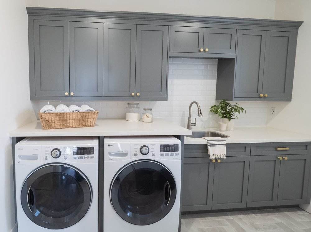 Going for something a little different:  deep gray laundry room shaker cabinets  with something familiar,  white beveled subway backsplash tile .