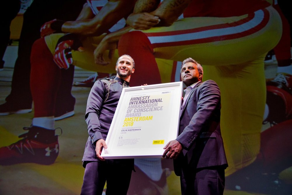 Colin Kaepernick accepts the Amnesty International Ambassador of Conscience Award for 2018 from the human rights organization's secretary general, Salil Shetty, on Saturday in Amsterdam.