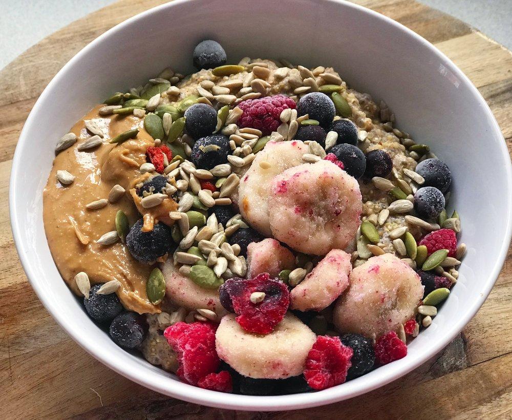 Quinoa porridge with cashew butter, frozen berries, banana and seeds.