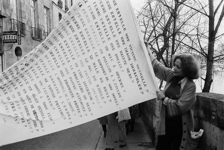 Lea Lublin (Poland/France/Argentina) handling her poster  Ist Kunst (Interrogations sur l'art)  , 1975 in Paris.