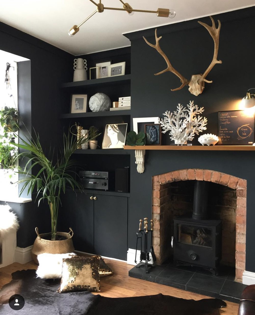 "A particular favourite of mine is Nadia's front room, when I visited in November, this fire was on and this whole room was cosy an inviting. I particularly like the dark walls (naturally given my own taste) but love the use of the lighter and warm colours against it. You will see the use of gold is a theme throughout the house. ""The antlers are from a local deer park,"" Nadia shares. ""They were so big I could barely carry them."""
