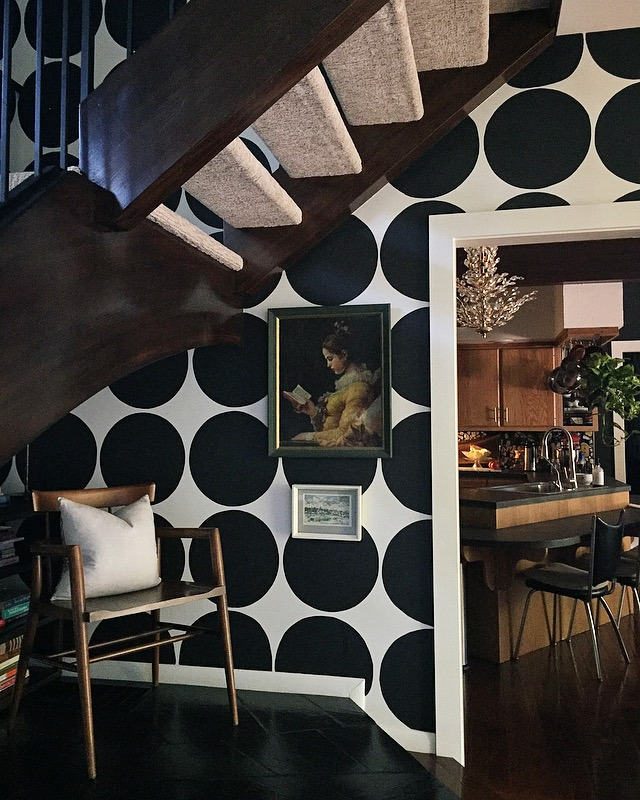 """One of my favorite architectural details in our home; we love this ""book nook"" under the stairs."" says Andrea. ""Features: original slate flooring, vintage MCM chair; collected art and circle wall that I painted a few years ago. Peek into our original 1964 kitchen that I love and hate at times, but Reno for that will come later 🖤"""