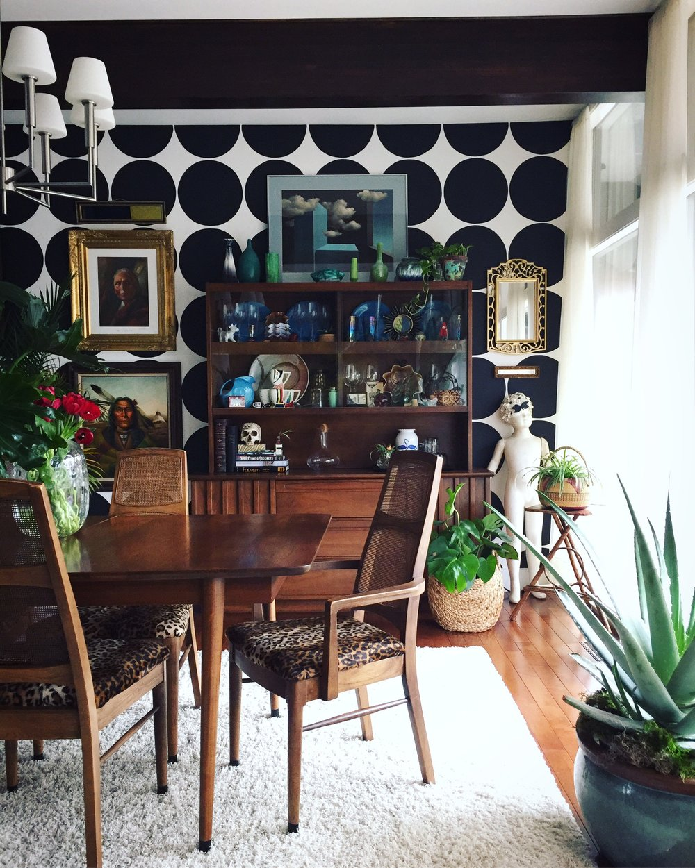 "Andrea says ""This inherited MCM dining set has been with my husband and I since our early married years and we still adore it. A space should tell a story; who you are, where you've been and what you hope to become. ""  ""I think our dining room showcases and curates a few of our experiences. The over stuffed hutch holds many of my prized treasures; one of my favorites: antique paper weights gifted from my grandfather. The table and chairs are all original except for the leopard print cushions (that I recovered), chandelier is by Sonneman Lighting, art has been collected over many years as have my plants.""  ""Another feature to our home we adore: the floor to ceiling windows"""