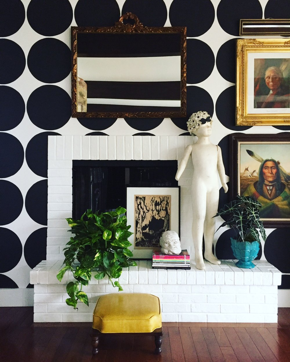 """This double sided fireplace (other side in family Room) had horrid brown brick originally. "" says Andrea. ""After many, many coats of white paint it was transformed! Features: antique French mirror, collected art and my quirky mannequin that we've named Joey."""