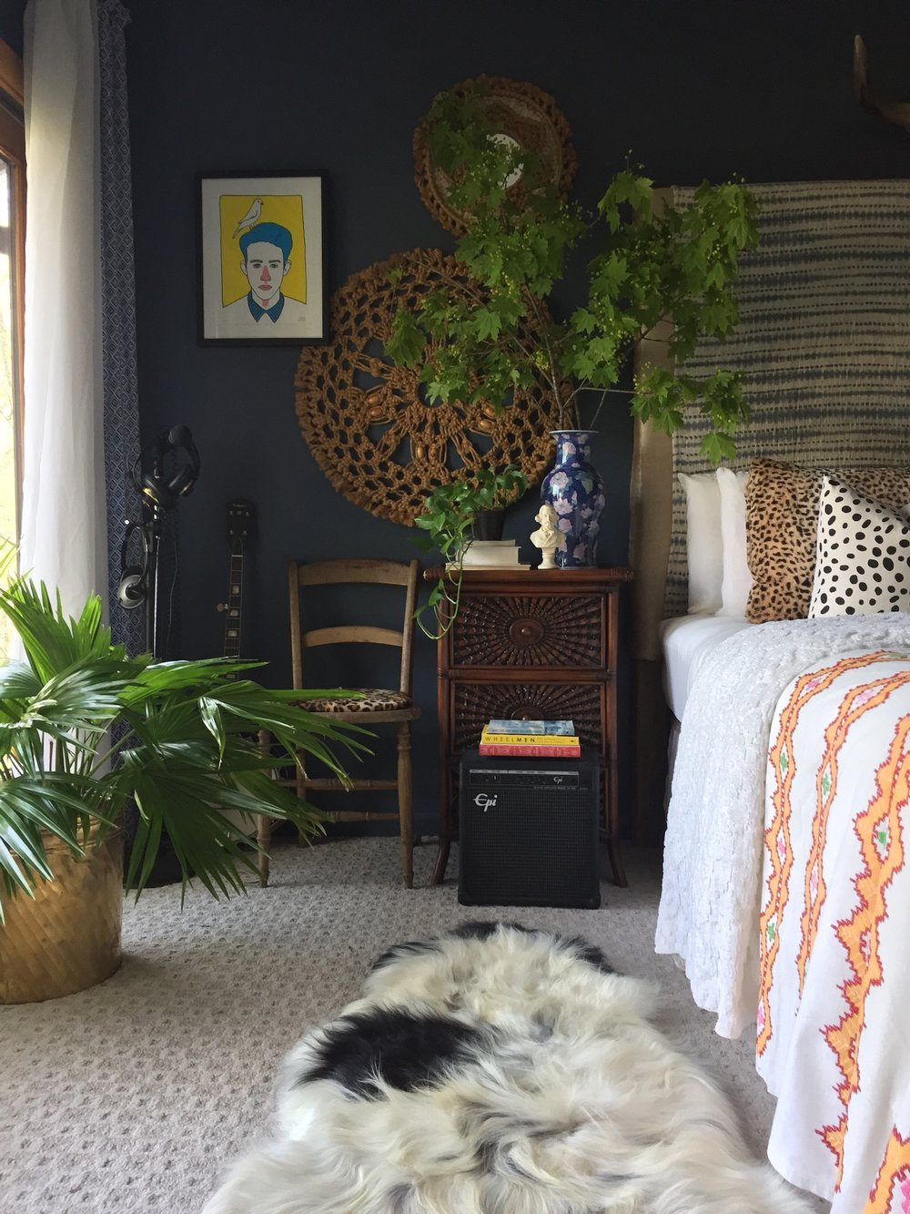 """Textile galore in here! On the bed is a chenille bedspread that belonged to my grandmother, topped with a fun retro tablecloth. The art is vintage macrame foundat a local thrift shop and the lithograph my husband and I purchased in Barcelona. One floor, my loved @cowboykate sheepskin."""