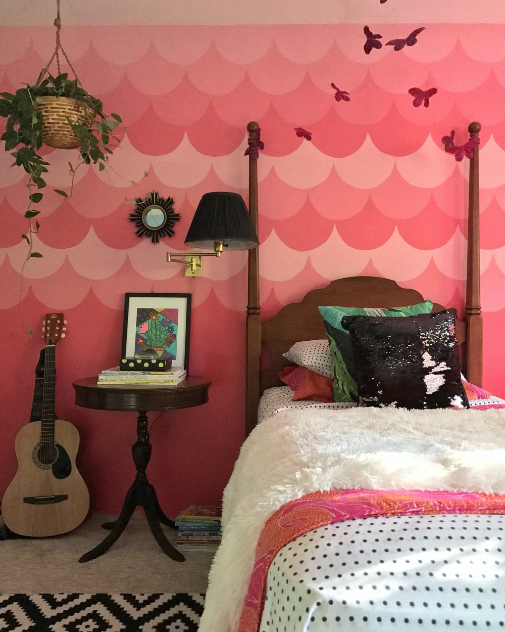 """I really allowed her creative freedom with this space."" says Andrea of her daughter Matilda's room. ""Her requests included: black/white, plants, sequins and my jungle pillow from @coppercorners.""  ""I wanted To create a space that  1. Encouraged her to want to be in it!    2. An environment that nurtured her imagination  3. And lastly, something that represented her story, or what she currently finds the most important in her young life.""    ""The scallop wall was a labor of love for this ""not so keen on pink"" gal, but it has grown on me. The bed frame was mine as a child, the bedding is a mix of DVF home, target and vintage. The side table and arm lamp were both thrift finds that I spruced up."""