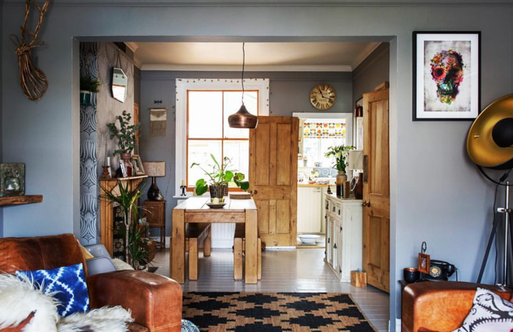 A view from the living room to the kitchen, with two rooms knocked together, painted in a lovely soft grey and with wooden doors and furniture complimenting the look and leather chairs, to snuggle down in.