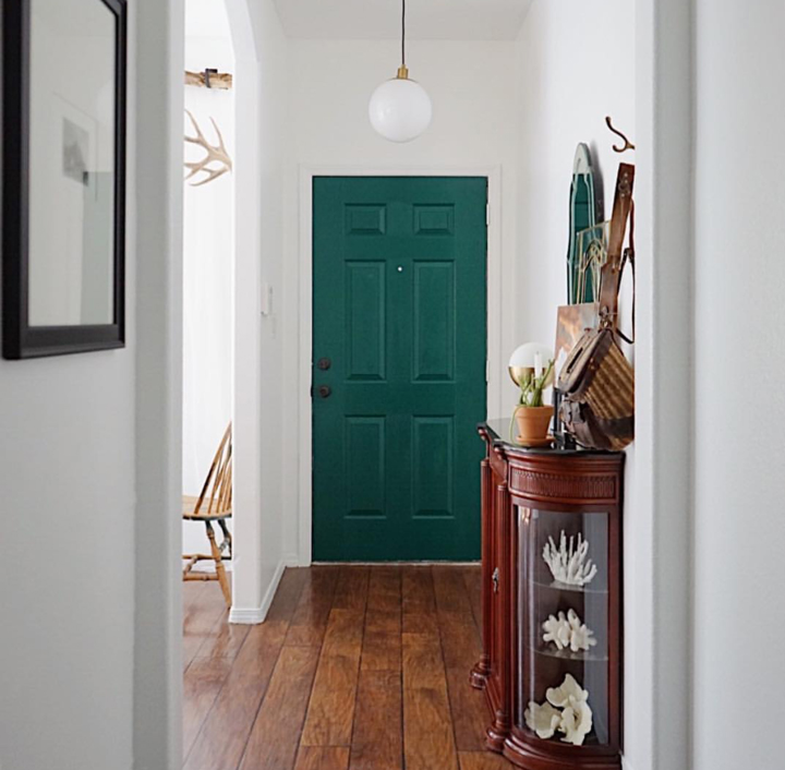 A long thin hallway, set of beautifully by this vibrant green door; it used to be pink.
