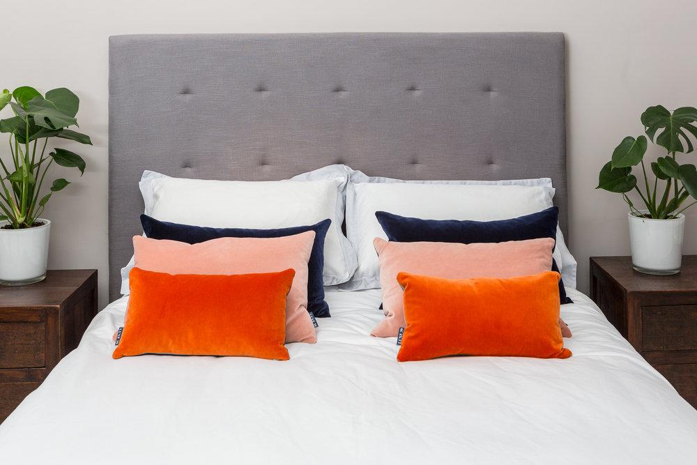 Orange, Blush & Navy cushions on bed copy.jpg