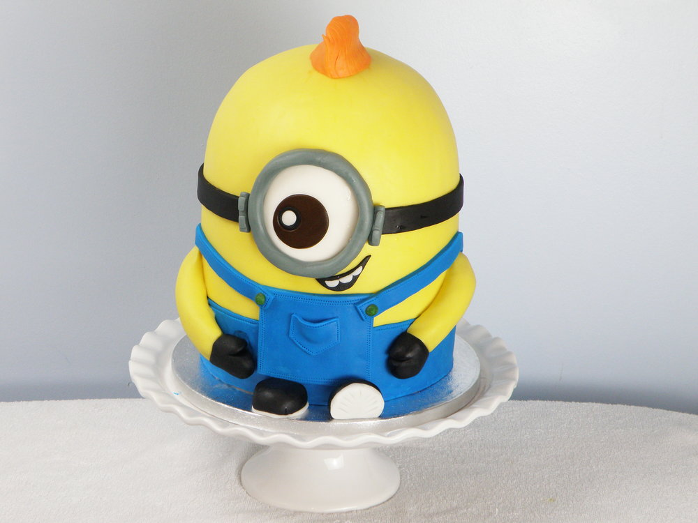 "Minion cake   8 layers of vanilla sponge filled with chocolate ganach and vanilla mousseline buttercream.  8""/10""   £""98"
