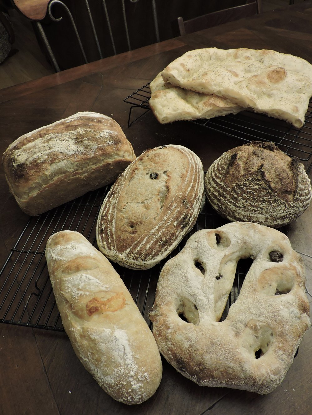 Rosemary focaccia (far back), then standard sourdough sandwich (middle far left), golden raisin fennel (middle), stout sourdough (middle far right), Dubliner cheddar batard (front left), and olive fougasse (front right).