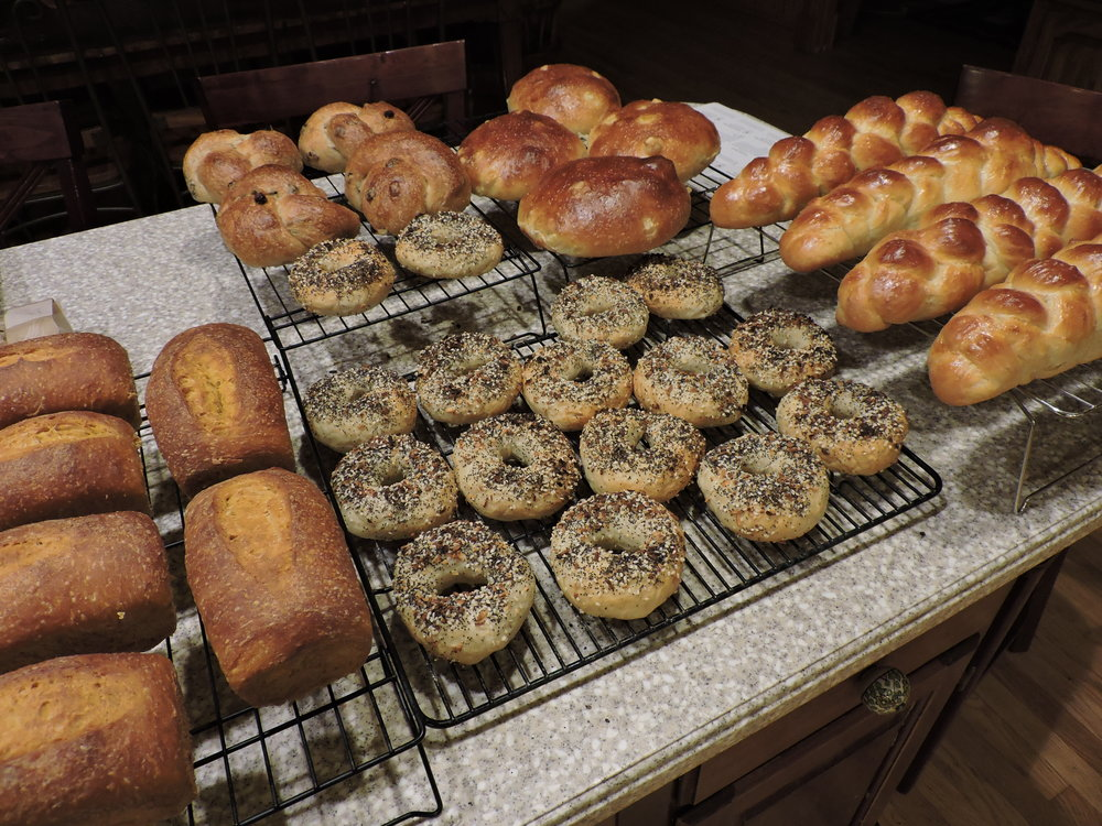 Pumpkin loaves (left), everything bagels (middle), cinnamon raisin knots (back left), apple honey challahs (back right), and plain challah braids (right).