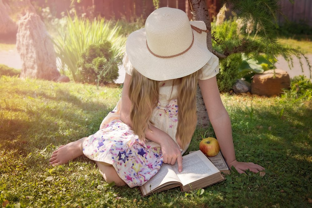 Young Girl in a Sun Hat Reading a Book in a Park