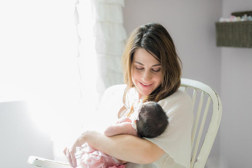 New mom rocking her newborn baby girl in nursery