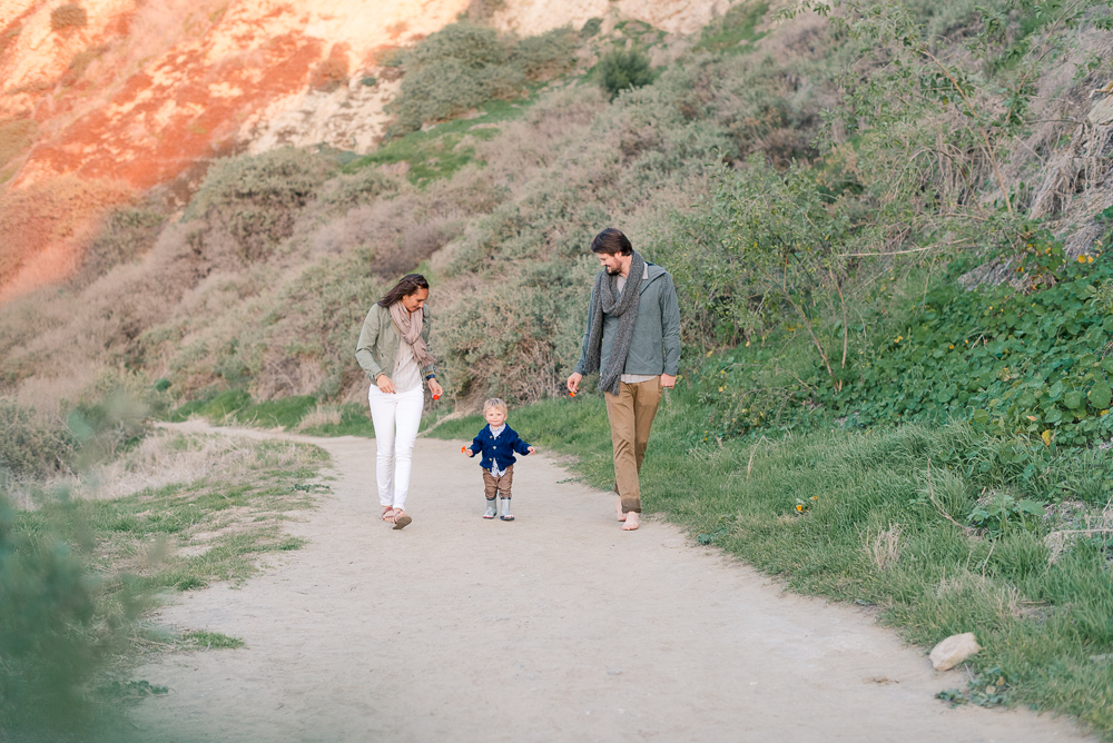 photo of family walking at the beach
