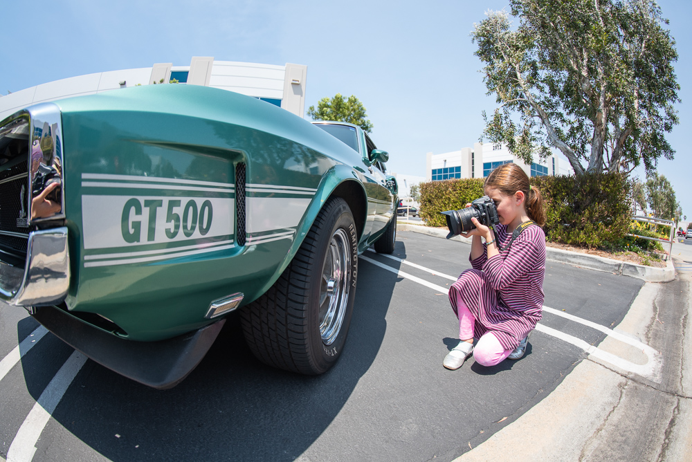 girl using nikon to take picture of an old car