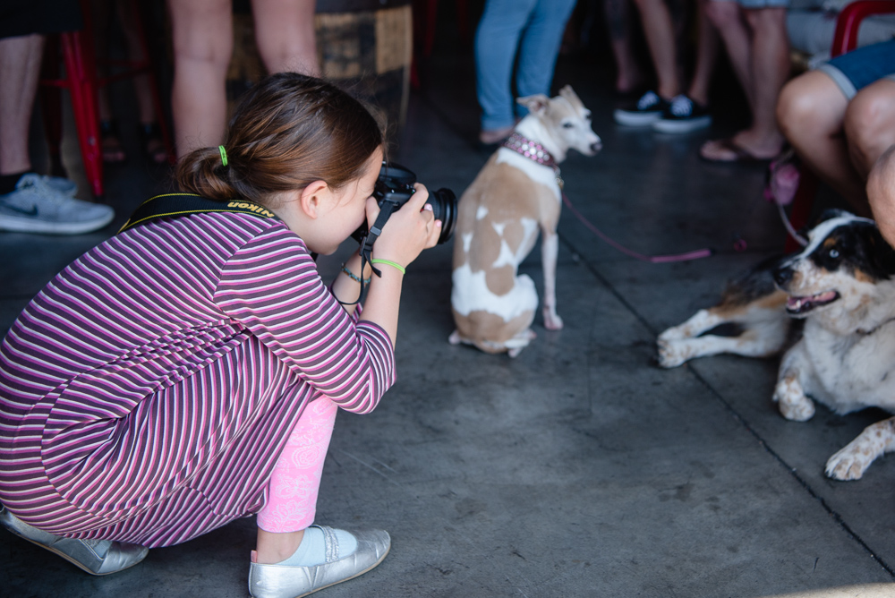 girl taking photograph of dog