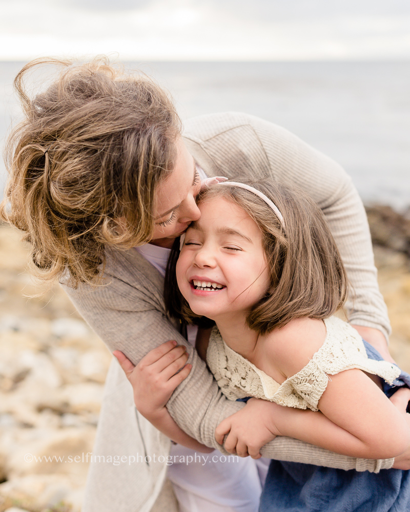 mother and daughter hugging and laughing