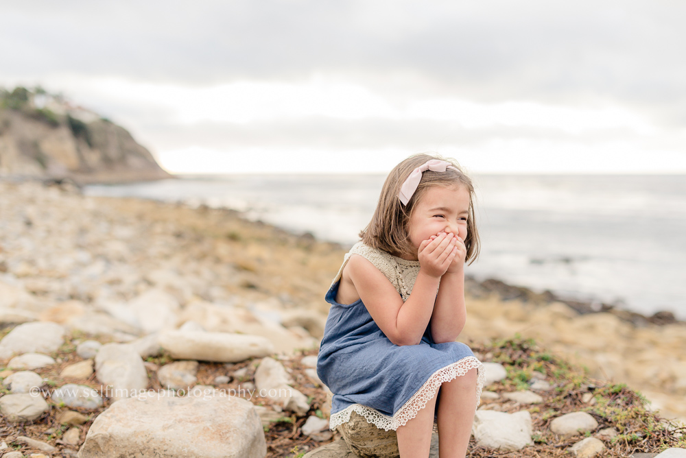 little girl sitting at the beach laughing