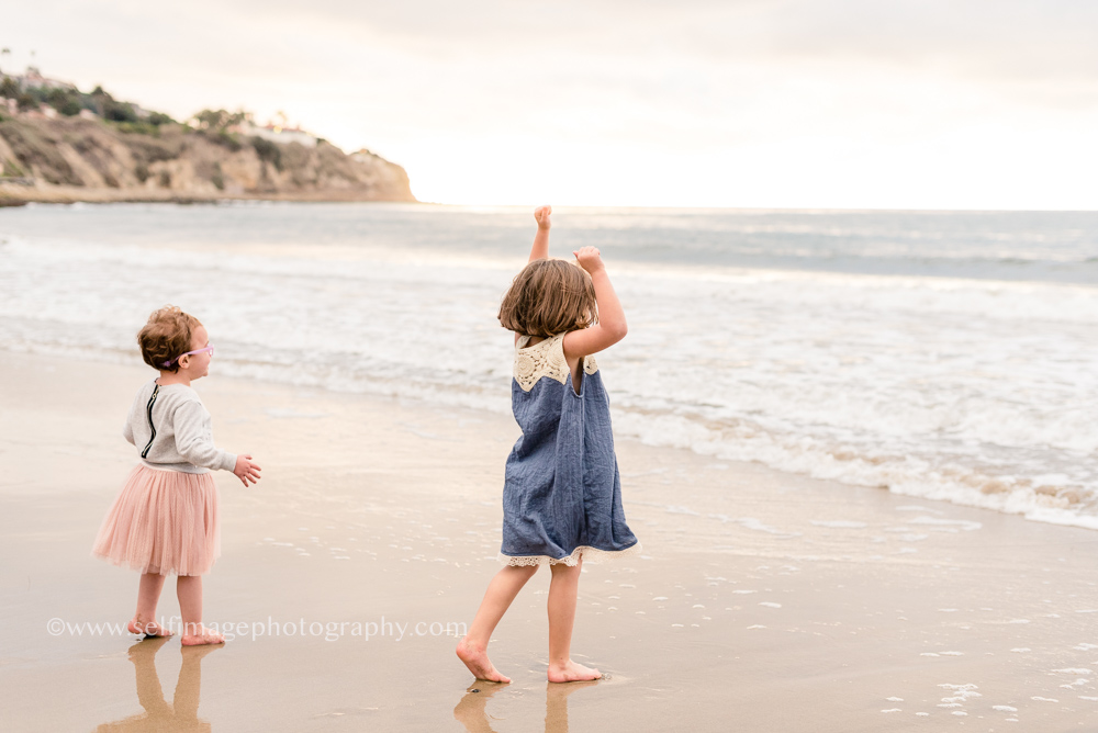 sisters standing at the edge of the shore